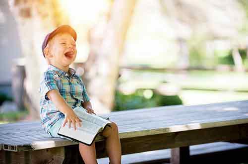 Happy little boy reading a book