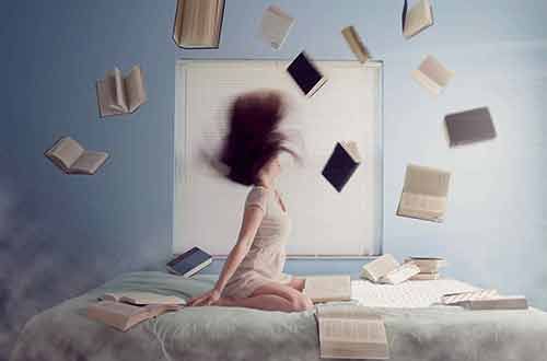 Happy Girl in bed throwing books in the air
